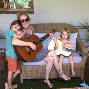 Astrid pictured seated on a wicker loveseat with two young children, and holding guitars.
